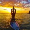 Le stand up paddle yoga permet une pratique des postures du yoga tout en profitant de la nature et d'un renforcement musculaire